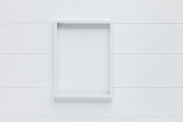 Empty frame for photo on white trendy wooden background. Place for text, copyspace