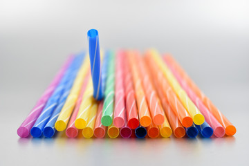 Plastic straw stock images. Harmful plastic straws. Colored straws. Plastic colored straws on a gray background. Colored drinking straws
