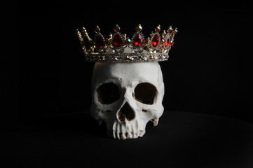portrait of a human skull wearing golden crown, photographed on black studio background.