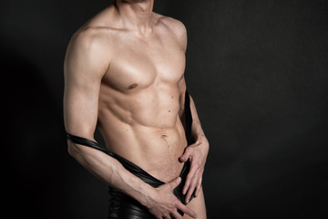 Sexy man without a shirt. Black background.
