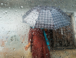 Monsoon season in Kathmandu, Nepal. Woman holding an umbrella seen through a window. Focus on droplets on glass.