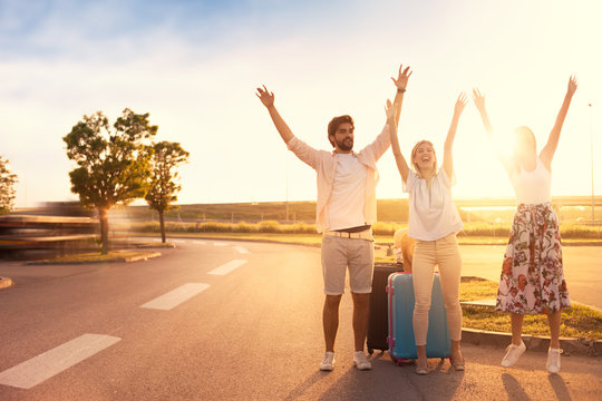 young hitchhikers happy because someone stopping to pick up them