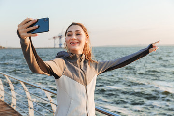 Excited young sportswoman taking selfie with mobile phone