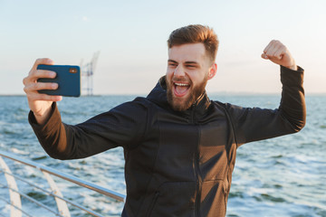 Excited young sportsman taking selfie with mobile phone