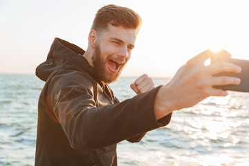 Happy young sportsman taking selfie with mobile phone