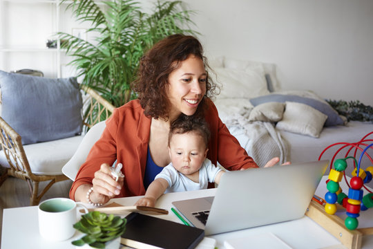 Attractive young dark skinned woman working at desk at home using laptop, holding baby on her lap. Portrait of smiling mother writing post on moms blog while her infant son playing with toy