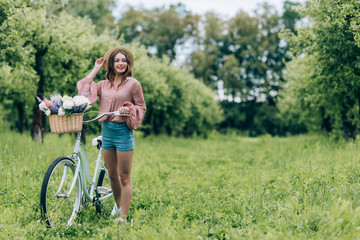 young pretty woman holding retro bicycle with wicker basket full of flowers in forest