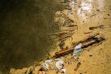 Close up view from above of polluted dirty muddy water with debris, garbage and plastic.