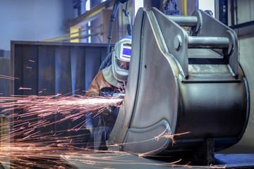Worker grinding metal in engineering factory
