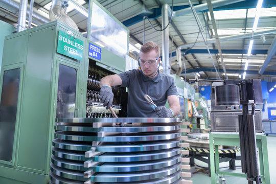 Engineer loading steel into pressing machine in metal pressing factory