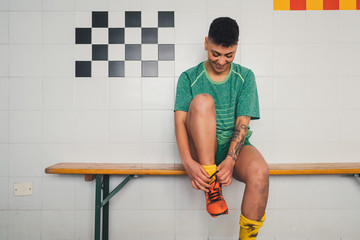 Football player tying shoelace on bench in changing room
