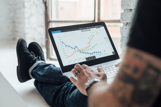 Man looking at graphical data on laptop