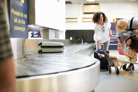 Family collecting suitcase from carousel in airport