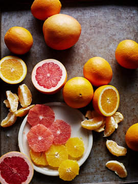 Still life with oranges and grapefruit, whole halved and sliced, overhead view