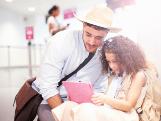 Father and daughter sitting at airport, looking at digital tablet