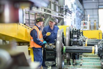 Engineer instructing apprentice with locomotive wheels in train engineering factory