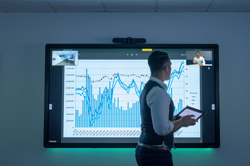 Businessman using video conferencing with graph on interactive screen in business meeting