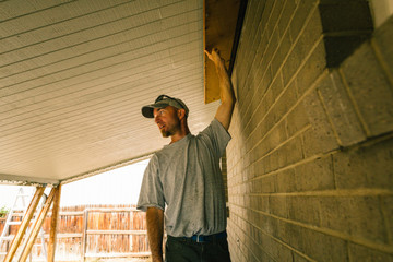 Electrician holding up wooden beam in porch
