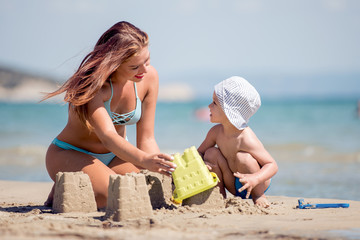 Mom and son are playing on the beach