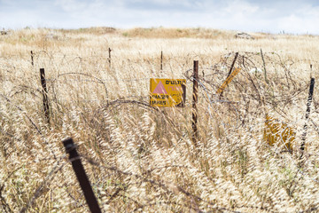 """A sign  reading """"Danger Mines!"""" hangs from a barbed wire fence in the Golan Heights, near the border with Syria, Israel"""