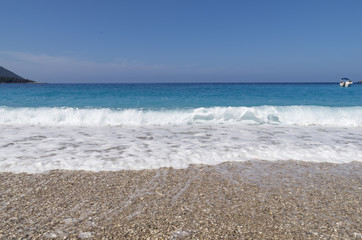 Pebble beach, white sea foam, turquoise sea with a small yacht and blue sky