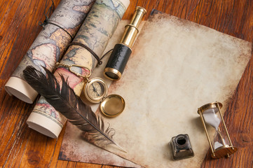 Quill pen on old paper sheets with old rolled maps and vintage items