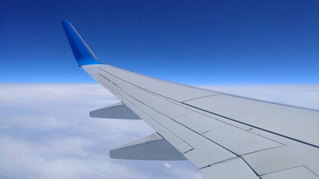 View of a gray airplane wing through the aircraft window