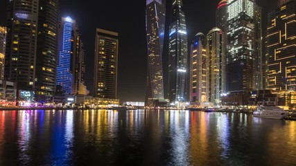 Fototapete - Night time lapse of moving tourists boats in canal of Dubai Marina