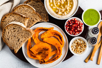 vegan appetizer snack from hummus of white cannellini beans and baked pumpkin on a serving board. Just great food