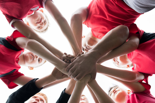 Low angle closeup of junior football team stacking hands during motivational pep talk before match in outdoor stadium, copy space