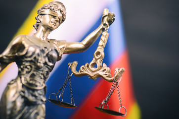 Scales of Justice, Justitia, Lady Justice in front of the Russian flag in the background.