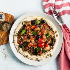 vegan panzanella salad on a layer of hummus on a plate. tasty healthy food.