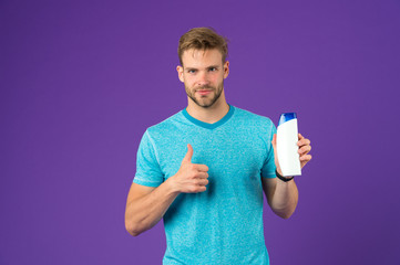 Man show thumbs up with shampoo bottle on violet background. Bearded man like gel tube on purple background. Skincare and hair care. Health and healthcare. Cosmetic for spa and bath or shower