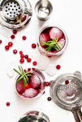 Cranberry cocktail with ice, rosemary and berries, bar tools, white background, top view