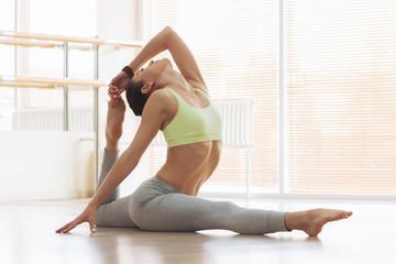 Young woman doing yoga on floor