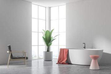 White tub in a white bathroom, armchair corner