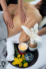 Massage series: Therapist massaging Asian woman's back with hot wax