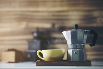 cup of coffee with metal coffee percolator on wooden background,