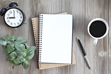 Still life, business, planning or working concept : Open notebook with blank pages, coffee cup and clock on wooden desk table, top view or flat lay with copy space ready for adding or mock up