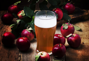 Apple cider in a large beer glass, vintage wooden background, selective focus