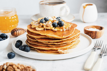 Pancakes with nuts, honey and fruits for breakfast. Stack of american pancakes. Tasty pancakes on white plate, closeup view, selective focus