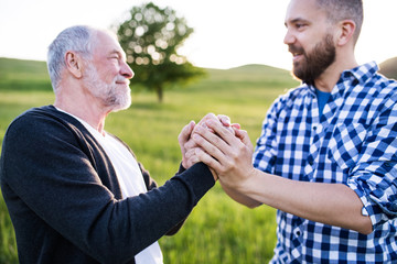 An adult hipster son with senior father on a walk in nature at sunset.