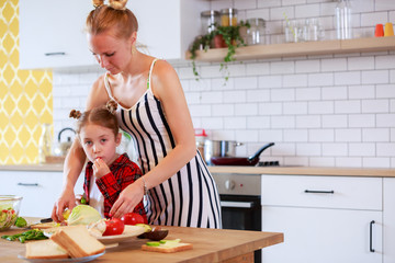 Picture of young mother with her daughter cutting vegetables in kitchen