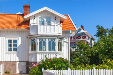 Idyllic white wooden house with garden in summer