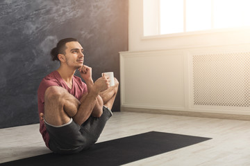 Young man in flexible yoga pose drinking tea