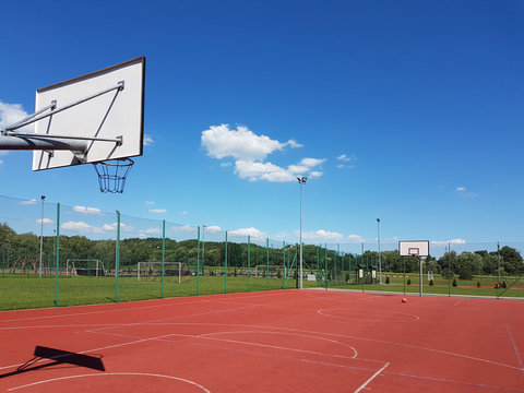 Modern basketball court under the open sky with artificial red coating. Location of team sports events. Physical education of citizens. Healthy lifestyle. Urban infrastructure for recreation, interest