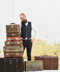 Macho elegant on tired face, exhausted at end of packing, leans on pile of vintage suitcases. Baggage and relocation concept. Man with beard and mustache packed luggage, white interior background.
