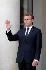 French President Emmanuel Macron waves to a guest at the Elysee Palace in Paris