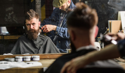 Barber with clipper trimming hair on nape of client. Hipster hairstyle concept. Hipster client getting haircut. Reflexion of barber with hair clipper works on haircut of guy, barbershop background