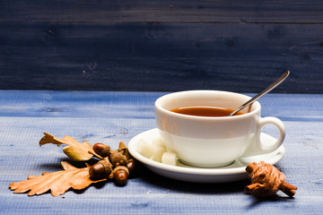 Drink and acorn and oak leaves. Tea served with spoon, sugar and decor as cinnamon. Mug filled with black brewed tea, spoon and autumn fallen leaves on blue wooden background. Autumn drink concept